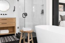 a chic fancy bathroom with a black hex tile floor, an oval tub, wooden furniture and a striped rug plus a glass enclosed shower