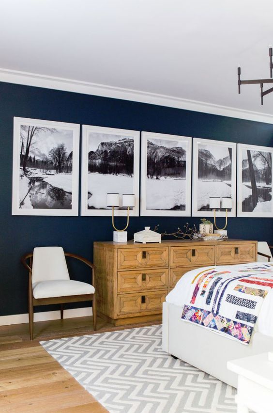 a chic farmhouse bedroom with a navy accent wall, a black and white gallery wall, a stained dresser with inlays, a comfy bed and pretty chairs