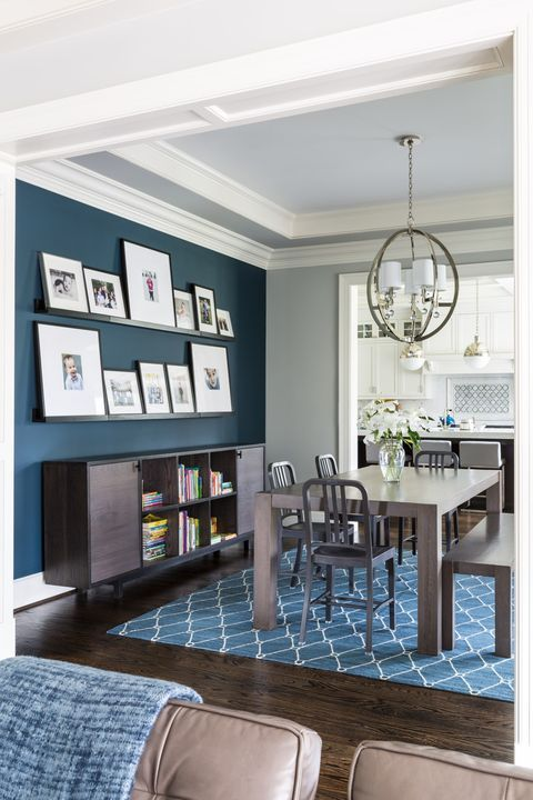 a chic farmhouse dining room with a navy accent wall, dark stained furniture, a gallery wall on ledges and a sphere pendant lamp