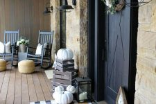 a chic farmhouse porch with navy rockers and white pillows, a plaid rug, crates and lots of pumpkins, a wreath and blooms for the fall