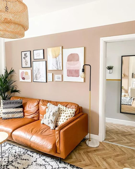 a chic living room with a blush accent wall, an amber leather sofa, a gallery wall, printed pillows and a rug plus a woven pendant lamp