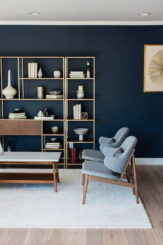 a chic living room with a navy accent wall, a gilded storage unit, grey upholstered chairs and a long table plus a neutral rug