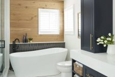 a chic modern country bathroom with a stained wood wall, a black tile accent, navy shaker style cabinets, white appliances and black fixtures