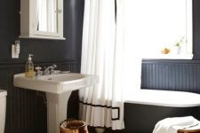 a chic modern country bathroom with black walls and paneling, white penny tiles, a black clawfoot tub, a vintage free-standing sink