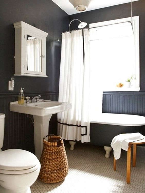 a chic modern country bathroom with black walls and paneling, white penny tiles, a black clawfoot tub, a vintage free standing sink