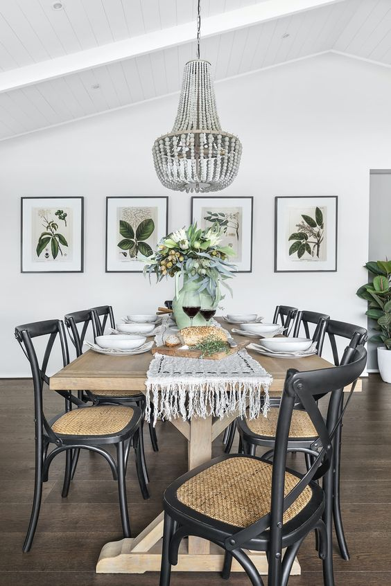 a chic modern country dining room with a stained table, black woven chairs, a wooden bead chandelier, a mini gallery wall