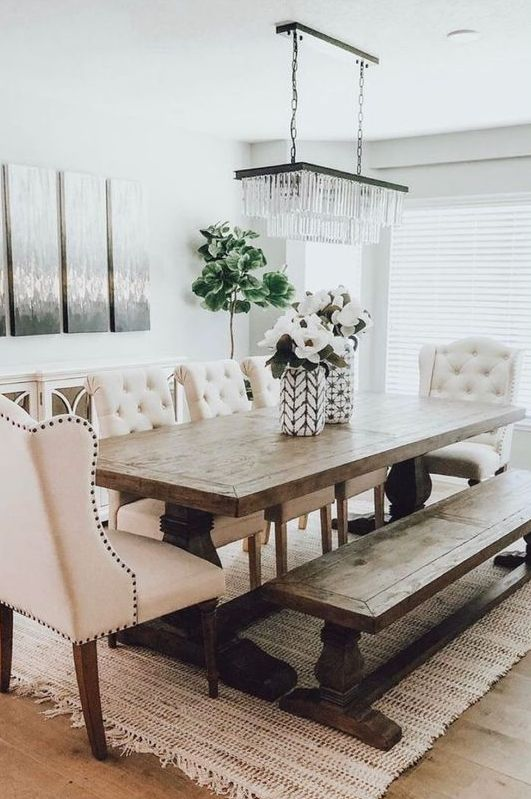 a chic modern country dining room with white walls, a vintage wooden table and a bench, tufted chairs and a lovely crystal chandelier