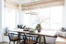 a chic modern country dining space with a built-in banquette seating, a stained table, black chairs and woven shades