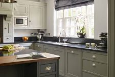 a chic modern country kitchen in olive green, with black and butcherblock countertops, a vintage pendant lamp and shiny knobs