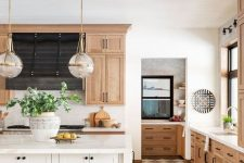 a chic modern country kitchen with light stained cabinets and hardwood floors, a white kitchen island, tall stools and pendant lamps