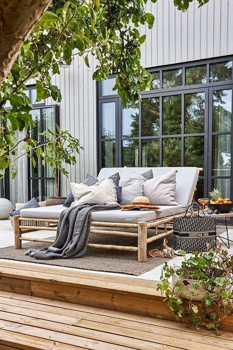 a chic modern country terrace with a wooden deck, rattan furniture, small side tables, lots of greenery around and lots of pillows