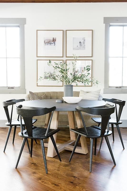 a chic modern farmhouse dining nook with a loveseat, a round table, black chairs, a chic gallery wall and greenery in a vase