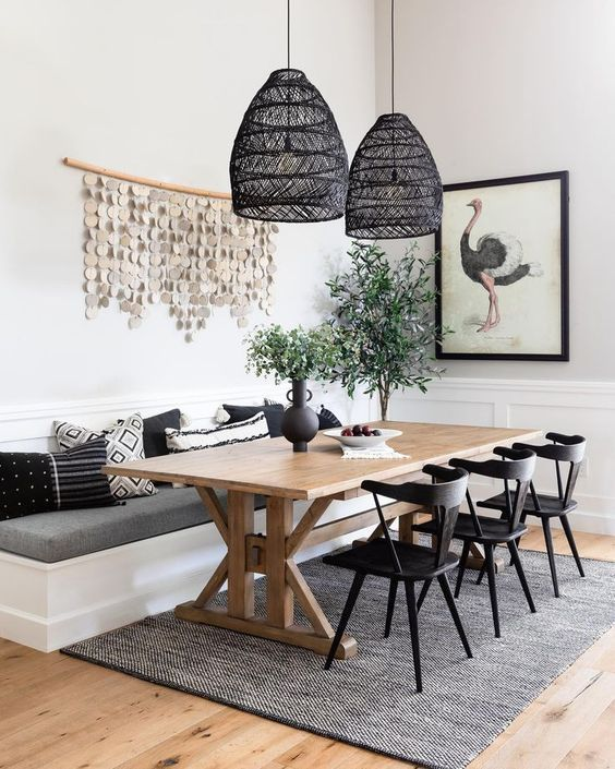 a chic modern farmhouse dining room with white paneled walls, a built-in banquette seating, a trestle dining table, black chairs and black woven pendant lamps