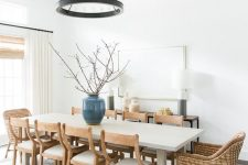 a chic modern farmhouse dining space with a large table, wooden and woven chairs, a metal chandelier and a console and lamps