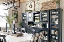 a chic modern farmhouse dining space with black storage units, a white vintage table and mismatching chairs plus a jar chandelier