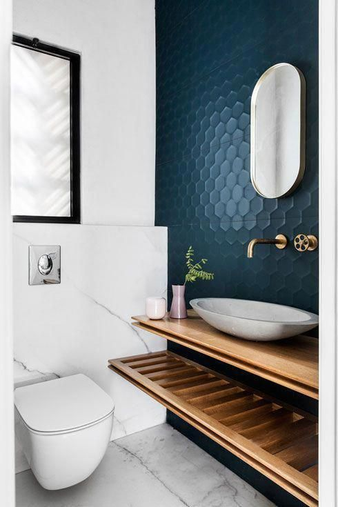 a chic modern restroom with a navy hexagon accent wall, floating shelves, a bowl sink and marble tiles cladding the wall and the floor