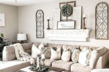 a chic neutral farmhouse living room with a tan sectional, a shelf with shutters and wooden candlesticks, a low coffee table