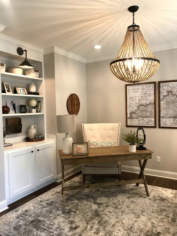 a clean and simple modern country home office with grey walls, a white storage unit, a trestle desk, a leather chair and a wooden bead chandelier
