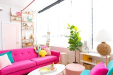 a colorful attic living room with a hot pink sofa, turquoise chairs, colorful and fun pillows, a potted plant and a blush pouf