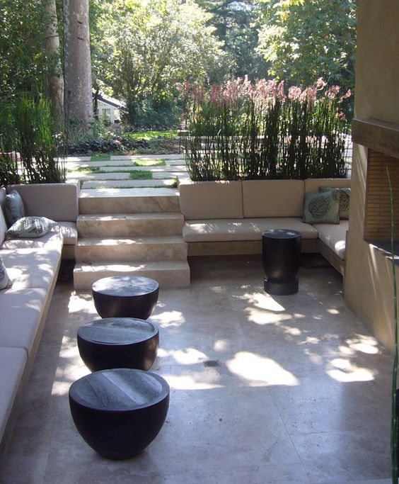 a contemporary sunken patio with a fireplace and built-in upholstered benches, small coffee tables and grass around it is great for relaxing