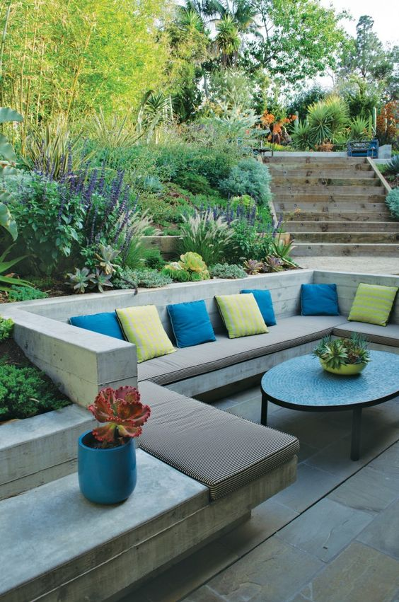 a contemporary sunken patio with built-in benches, colorful pillows and a coffee table plus greenery and blooms around