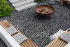 a contemporary sunken patio with gravel on the ground, built-in benches and a fire pit is amazing for spending nights here