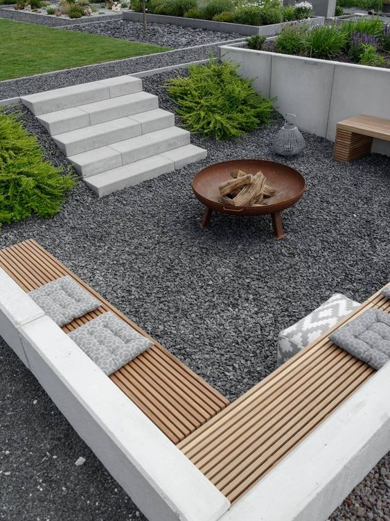 a contemporary sunken patio with gravel on the ground, built in benches and a fire pit is amazing for spending nights here