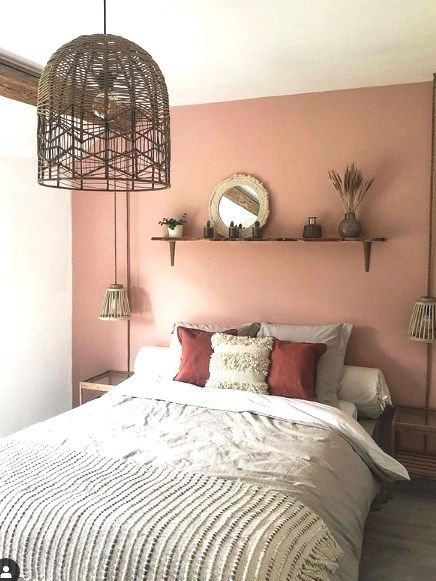 a cool boho bedroom with a pink accent wall, a comfy bed with pretty bedding, a little shelf with some decor and woven pendant lamps