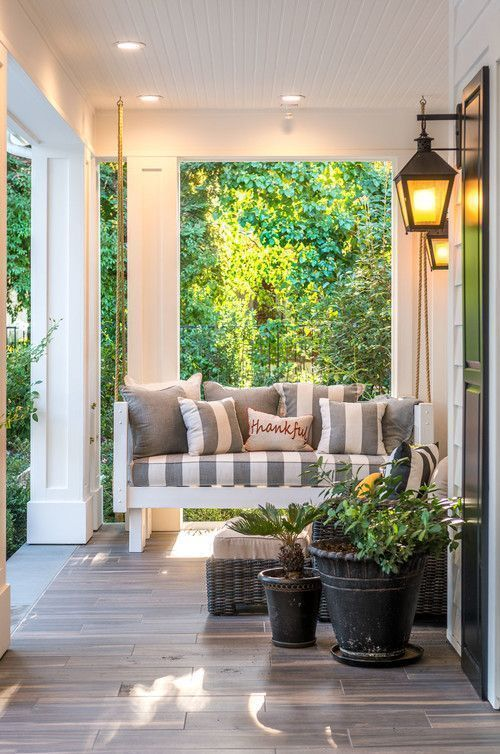 a cool farmhouse porch with a striped upholstered sofa, a wicker lounger, potted plants and greenery and lanterns on the walls