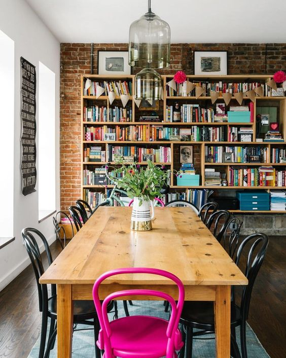 a cool industrial space with an extended brick wall, a wooden table, a bookshelf that takes a whole wlal and a hot pink chair for an accent