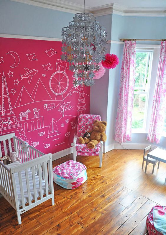 a cool kid's room with a hot pink accent wall, a crib and a comfy chair with a pouf, a white dining space and a floral chandelier