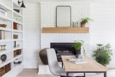 a cool modern country home office with a white brick fireplace, a large storage unit, a desk and a bold rug, potted plants