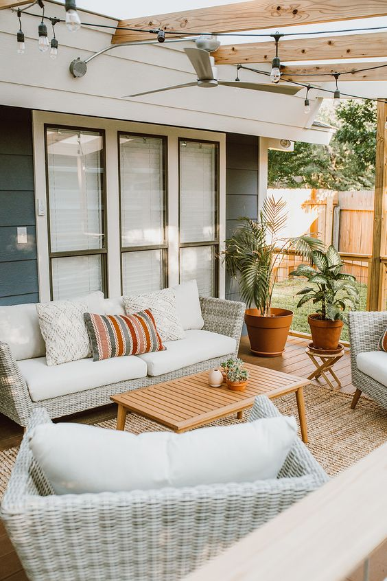 a cool modern country outdoor living room with neutral woven furniture, printed pillows, a wooden table and potted plants welcomes
