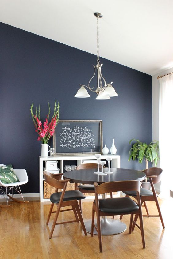 a cool modern dining room with a navy accent wall, a round table and black chairs, a storage unit, greenery and blooms