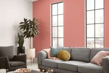 a cool modern living room with a pink accent wall, a grey sofa and colorful pilows, a black coffee table and a catchy chandelier