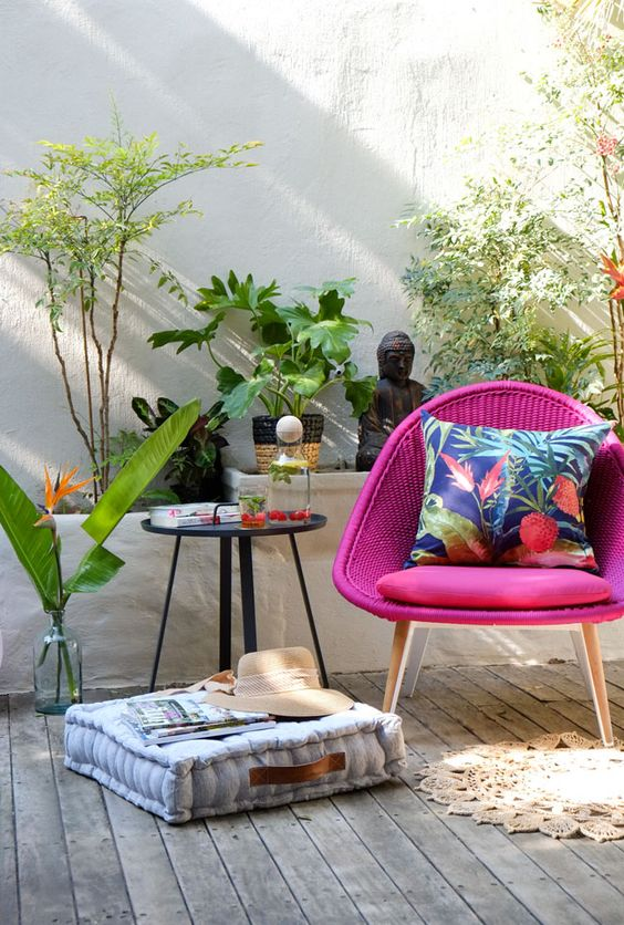 a cool outdoor nook with a woven hot pink chair, a side table, a cushion, potted plants and beautiful Asian-inspired decor