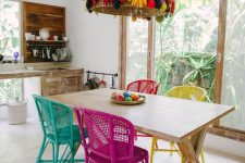 a crazy boho eat-in kitchen with whitewashed furniture, a shabby trestle table, a hot pink, turquoise, yellow and red chair and a jaw-dropping pendant lamp