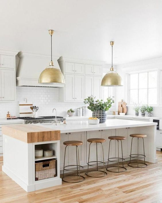 a creamy modern country kitchen with shaker style cabinets, a large kitchen island with storage, gold pendant lamps