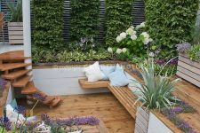 a creative sunken patio with living walls, greenery and blooms around, steps and a bench for sitting is a cool way to make use of a small space