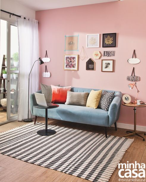 a cute modern living room with a pink accent wall and a gallery wall on it, a blue sofa, some coffee tables, printed textiles is sweet