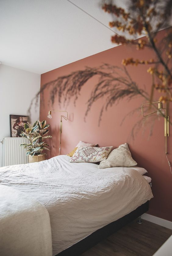 a dreamy and relaxed bedroom with a dusty pink accent wall, a bed and printed pillows, some potted plants and gilded sconces