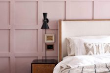 a dreamy bedroom with a pink panel accent wall, a bed with an accent headboard, a catchy nightstand and a chic black sconce plus a pink rug