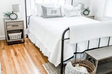 a dreamy farmhouse bedroom with a forged bed, wooden nightstands, a wooden bench and a basket for storage, some greenery
