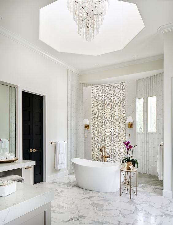 a fabulous fancy bathroom with white tiles and patterned ones, white marble tiles on the floor, a crystal chandelier and brass touches