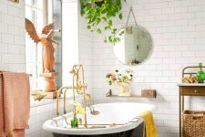 a fancy and whimsy bathroom with a gorgeous printed tile floor, a black vintage tub, a crystal chandelier and vintage furniture and a potted plant