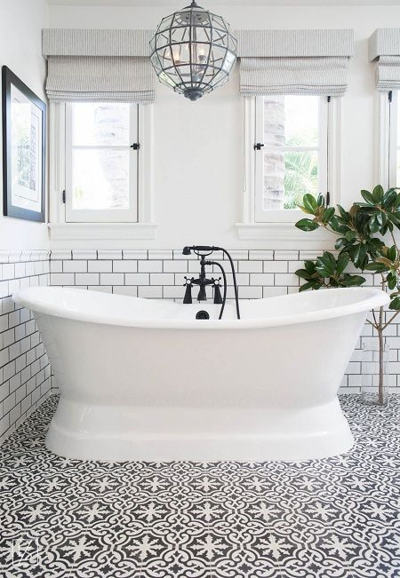 a fancy bathroom with a beautiful mosaic tile floor, a lovely tub and a chic faceted pendant lamp plus a statement plant