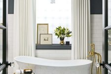 a luxorious bathroom with a black and white tile floor, white subway tiles and black walls, a chic tub, gold fixtures and a lovely chandelier