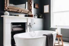 a fancy bathroom with black walls and a white planked floor, a fireplace used for storign towels, an oval tub and a mirror in a refined frame
