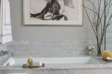 a fancy bathroom with grey marble tiles and marble itself, a crystla chandelier and a bold statement artwork just wows