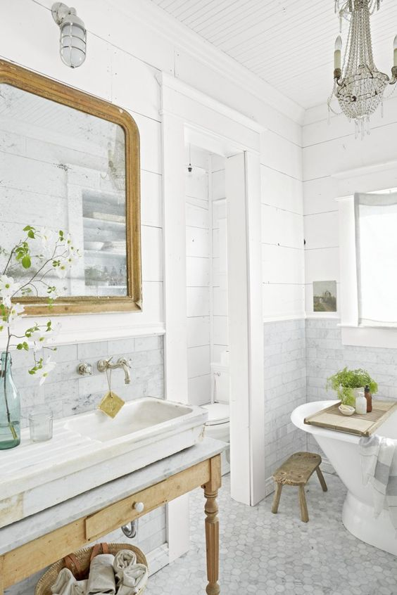 a fancy bathroom with grey marble tiles, planked walls, a vintage wooden vanity and a mirror in a wooden frame, a crystal chandelier and potted greenery